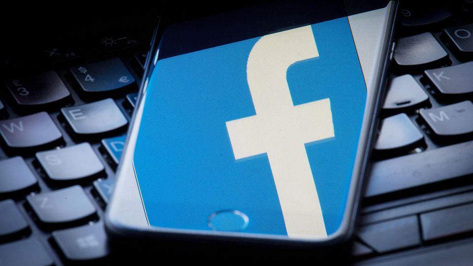 Das Facebook-Logo wird auf einem Smartphone gespiegelt