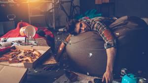 Ein Mann liegt auf einem Sitzkissen in einem unaufgeräumten Zimmer mit Essensresten