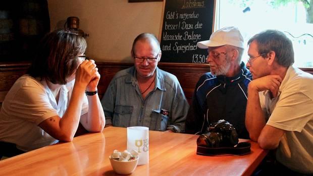 Melanie, Siegfried, Dieter und Frank (v.l.n.r.) sitzen gemeinsam in der Kneipe und unterhalten sich