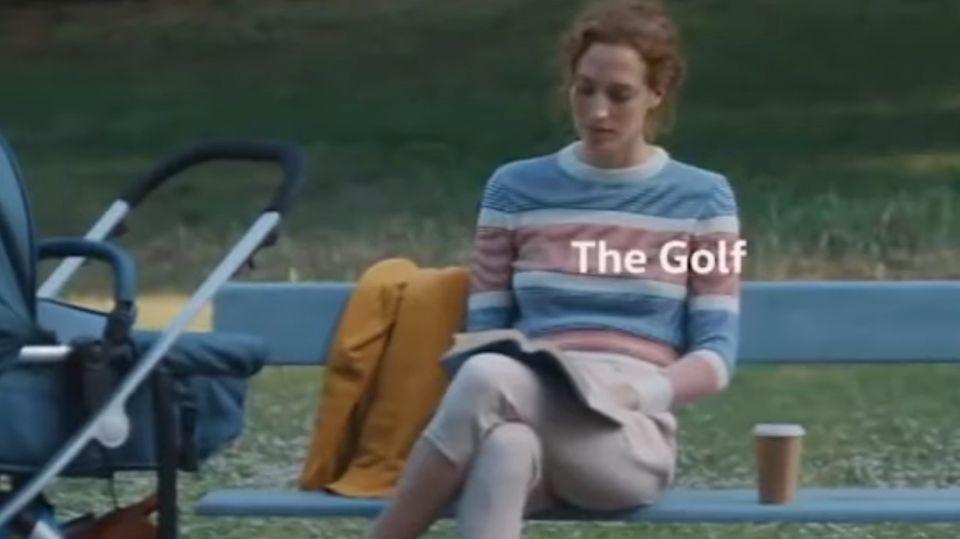 Eine Frau sitztlesend auf einer Parkbank, neben ihr steht ein Kinderwagen