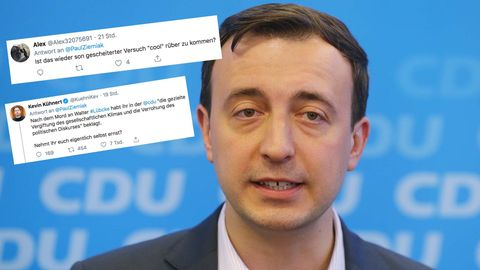 Ein Mann mit braunem Seitenscheitel steht in Hemd und Jackett vor einer blauen Wand mit CDU-Logos. Er spricht in vier Mikrofone