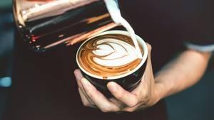 Krebsrisiko Kaffee? Ein Barista schüttet Milch in eine Tasse mit Kaffee