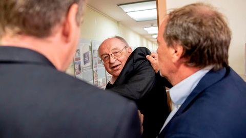 Zwei Männer in Anzügen schieben einen dritten Mann im Anzug aus der Tür