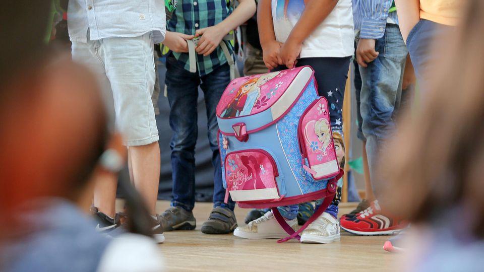 Kinder mit Schulranzen stehen beisammen