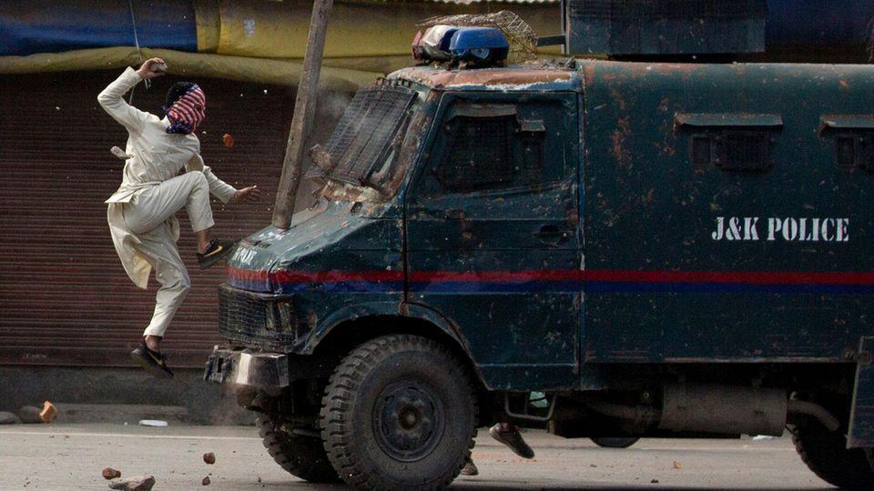 Ein maskierter Demonstrant springt auf ein gepanzertes Polizeifahrzeug, als er bei Protestenin dem von Indien kontrollierten KaschmirSteine auf das Fahrzeug wirft.