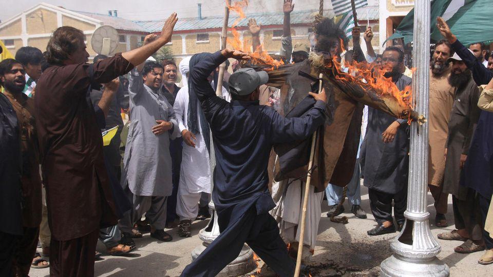 Ein Mann schlägt in der pakistanischen Stadt Quetta, auf ein brennendes Bild des indischen Premierministers Modi ein