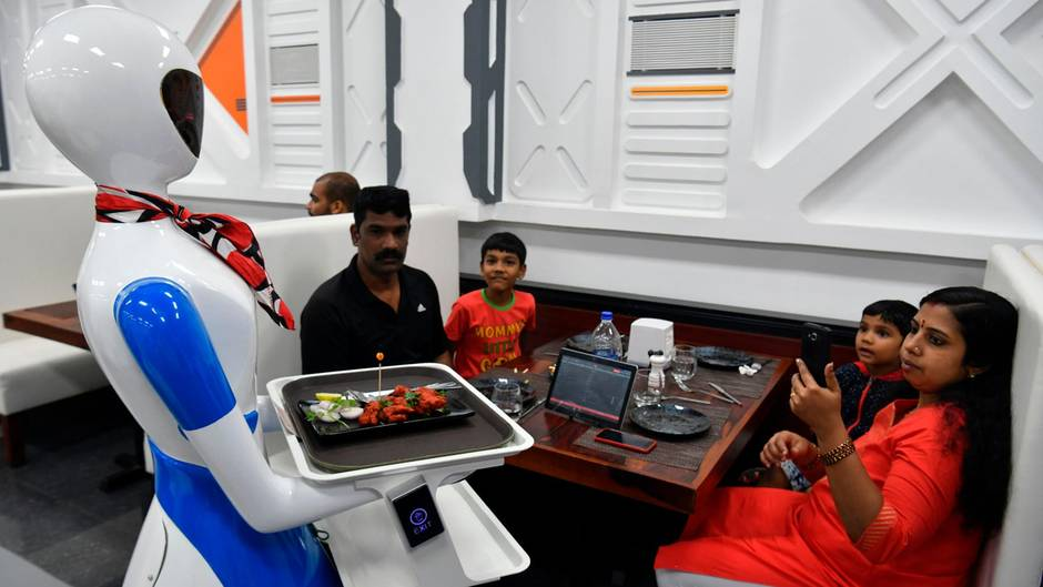 Bangalore, Indien. Ein Service-Roboter bedient eine Familie in einem Restaurant. Insgesamt arbeiten fünf künstliche Kellner und ein Türöffner dort.