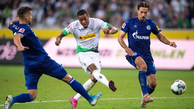 Gladbachs Alassane Plea (m.) schießt aufs Tor. Links läuft Schalkes Matija Nastasic und rechts Benjamin Stambouli