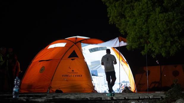 Ein Mann geht bei Dunkelheit in ein gut zwei Meter hohes Igluzelt, das orange zu leuchten scheint