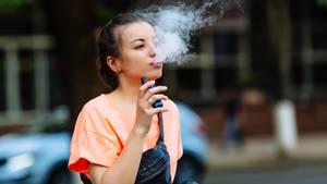 E-Zigarette: Eine junge Frau zieht an einer E-Zigarette