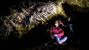 In einer dunklen Höhle sitzen zwei Männer mit Helmen und Stirnlampen. Eine der Lampen erhellt die Höhlendecke