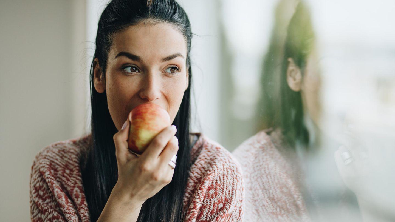 Flavonoide in Lebensmitteln: Eine Frau isst einen Apfel