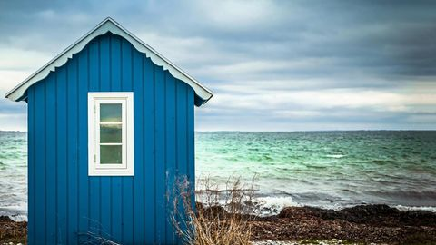 Blaues Badehäuschen mit Meer im Hintergrund