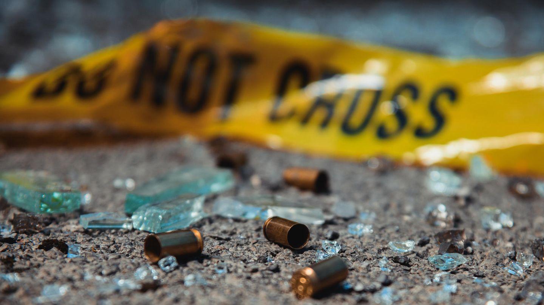 Leere Patronenhülsen und Glassplitter liegen auf dem Asphalt – im Hintergrund: ein Absperrband der Polizei