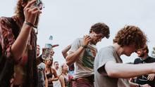 Drei Männer tanzen auf einem Festival