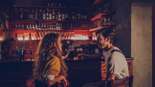 Mann und Frau sitzen an Bar