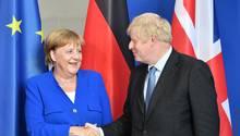 Vor den Flaggen der EU, Deutschlands und Großbritannien schüttelt Boris Johnson Bundeskanzlerin Angela Merkel die Hand
