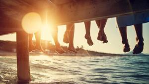 Menschen sitzen auf Steg am Wasser