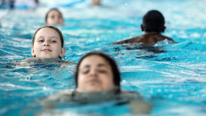 Schulkinder schwimmen im Becken