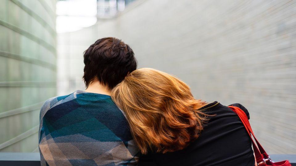 Frau lehnt sich an Schulter einer anderen Frau ab.