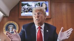 Donald Trump vor laufendem Fernseher in der PräsidentenmaschineAir Force One
