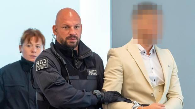 Ein Mann im weißen Anzug und Hemd wird von einem kahlköpfigen Polizisten mit Bart abgeführt