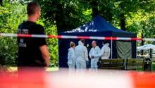 Ein Polizist sichert den abgesperrten Tatort, während vier Menschen in weißen Overalls offenbar Spuren sichern