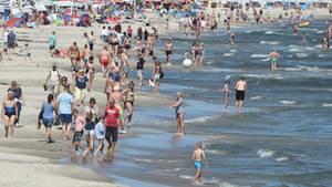 An einem Strand spazieren Badegäste an der Wasserkante entlang. Einige baden in der Ostsee