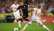 Marco Reus stürmt im schwarzen BVB-Dress mit Ball zwischen zwei Kölner Spielern in weiß hindurch