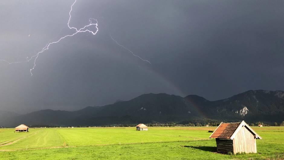 Ein Blitz zuckt über den bayerischen Voralpen, während über einer Weide ein Regenbogen erkennbar