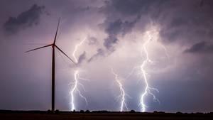 Unwetter am Nachthimmel über einem Feld mit einem Windrad.