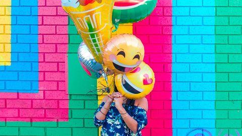 Frau mit Emoji-Ballons