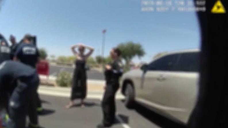 Unscharfes Bild zeigt eine Frau und Polizisten auf einem Parkplatz