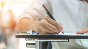 Eine Hand schreibt mit einem Stift auf ein Blatt Papier