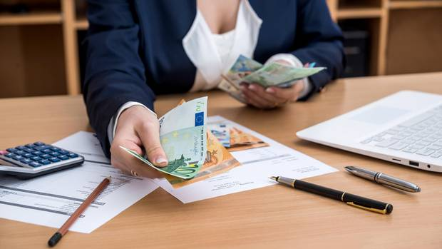 Frau teilt Geldscheine aus als Symbolfoto für Urlaubsanspruch bei Kündigung