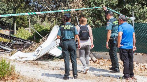 Ein Polizist hält ein Absperrband hoch, damit eine Frau mit Rucksack sich den Trümmern an der Absturzstelle nähern kann