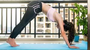 Eine junge Frau macht Yoga auf dem Balkon