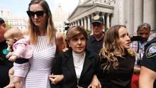 Drei Frauen gehen untergehakt durch eine Menschenmenge vor einem weißen Gerichtsgebäude mit Säulen