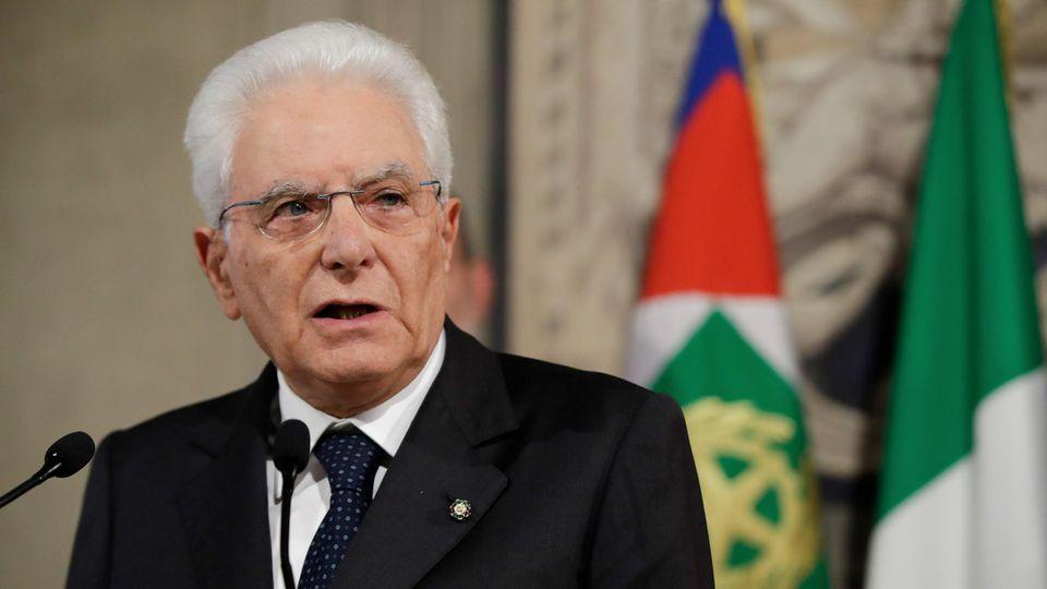 Ein weißhaariger Mann mit Brille spricht in mehrere schwarze Mikrofone. Hinter ihm sind Flaggen drappiert