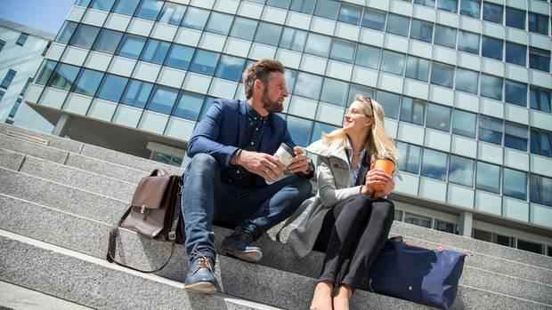 Mann und Frau sitzen vor einem Bürogebäude auf einer Treppe