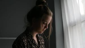 Woran erkennt man Depressionen? Frau steht traurig am Fenster
