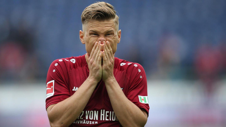 Ein Mann mit dunkelblondem Seitenscheitel steht im weinroten Trikot auf einem Fußballplatz und hält sich die Hände vor den Mund