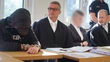 Der 19-jährige Angeklagte (l.) und der 21-jährige Angeklagte (3.v.l.) im Gerichtssaal im Landgericht neben ihren Anwälten