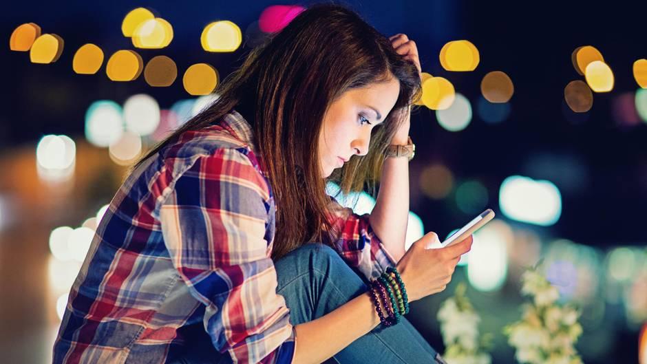 iPhone: eine junge Frau schaut auf ihr Smartphone