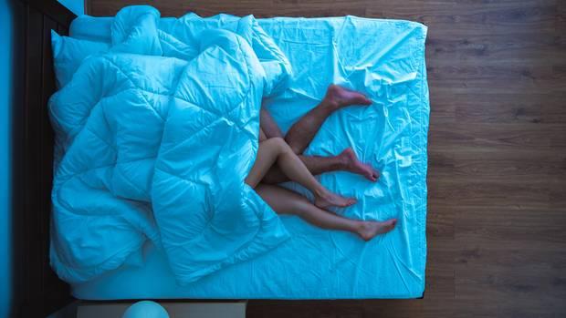 Zwei nackte Menschen liegen zusammen im Bett