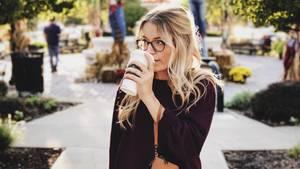Ein Frau steht allein auf einem Weg und trinkt Kaffee