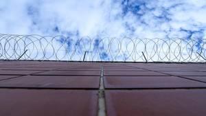 Stacheldrahtzaun hängt an einer Mauer in der JVA Weiterstadt