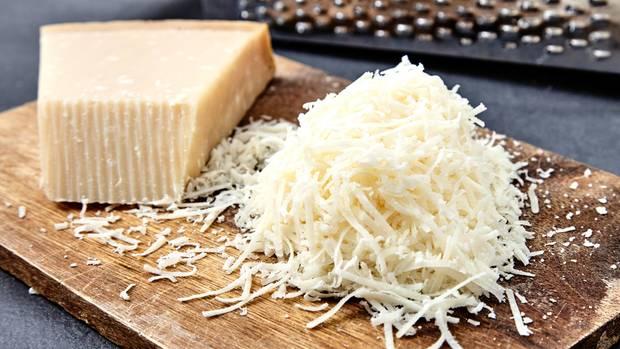 Parmesan im Check: Geriebener Parmesan liegt auf einem Holzbrett
