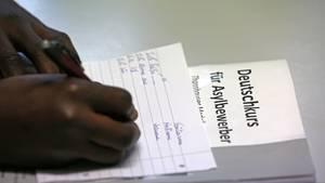 """Ein Afrikaner schreibt auf einem linierten Blatt. Darunter liegt ein Papier mit der Überschrift """"Deutschkurs für Asylbewerber""""."""