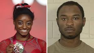 Links hält eine schwarze Frau in rotem Body eine Medaille in der rechten Hand. Rechts steht ein schwarzer Mann vor einer Mauer